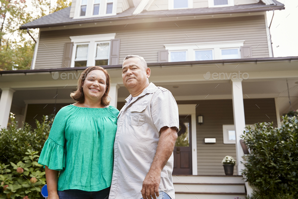 Portrait Of Smiling Senior Couple In Front Of Their Home - Stock Photo - Images