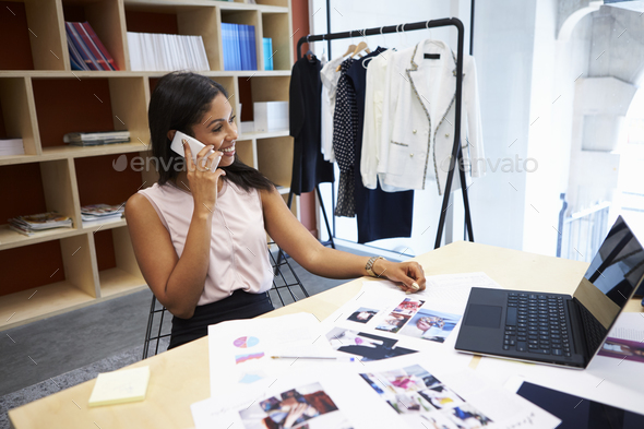 Young female media creative using smartphone in an office - Stock Photo - Images