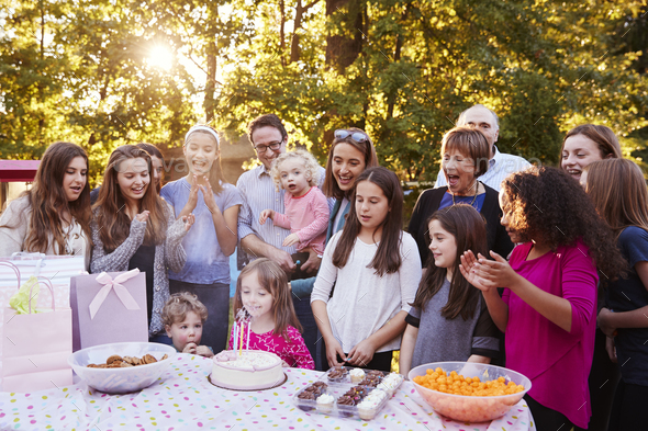 Young girl blowing out candles at her birthday garden party - Stock Photo - Images