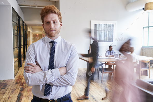Portrait of young red haired man in a busy modern workplace - Stock Photo - Images