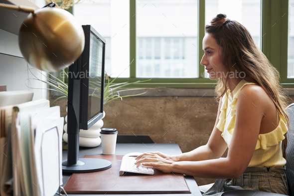 White woman working at a computer in an office, side view - Stock Photo - Images