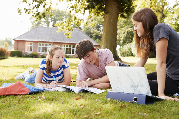 Teenage Students Sitting Outdoors And Working On Project - Stock Photo - Images