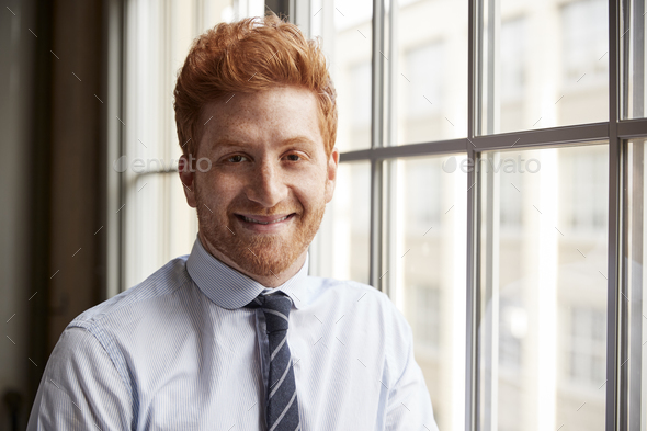 Young red haired bearded businessman smiling to camera - Stock Photo - Images