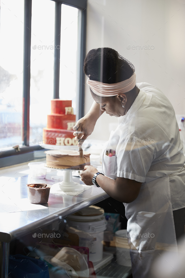 Young black woman frosting a cake at a bakery - Stock Photo - Images