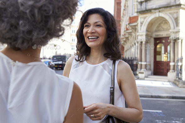 Two female friends talking in the street, close up - Stock Photo - Images