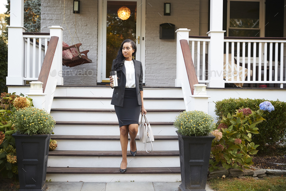 Businesswoman With Cup Of Coffee Leaving Suburban House For Work - Stock Photo - Images