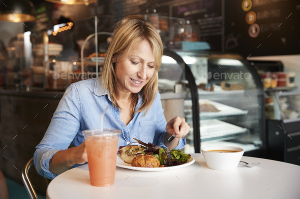 Woman In Coffee Shop Sitting At Table Eating Healthy Lunch - Stock Photo - Images