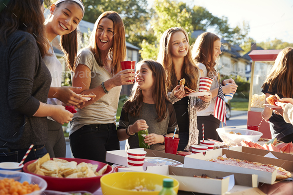 Girls stand talking at a block party food table, close up - Stock Photo - Images