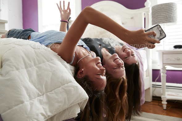 Three teenage girls lying on bed taking a selfie upside down - Stock Photo - Images
