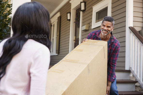 Couple Carrying Big Box Purchase Into House - Stock Photo - Images