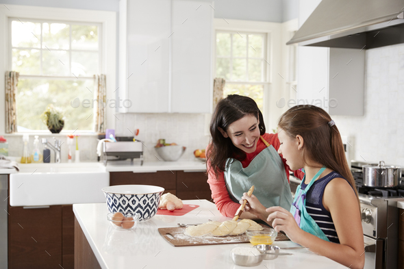 Jewish girl glazing plaited challah bread dough with her mum - Stock Photo - Images