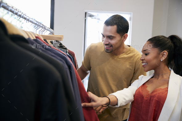 Young Hispanic couple looking at clothes in a clothes shop - Stock Photo - Images
