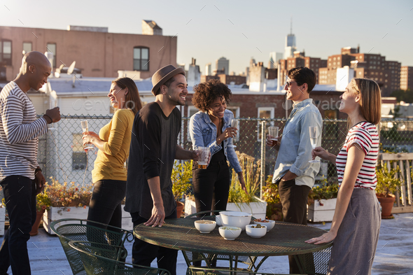 Friends stand talking at a party on a New York rooftop - Stock Photo - Images