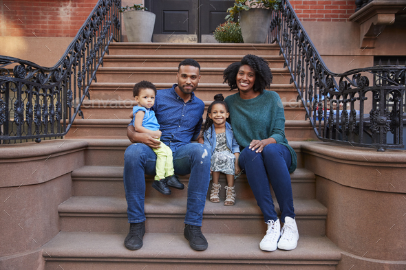Young family with kids sitting on front stoops - Stock Photo - Images