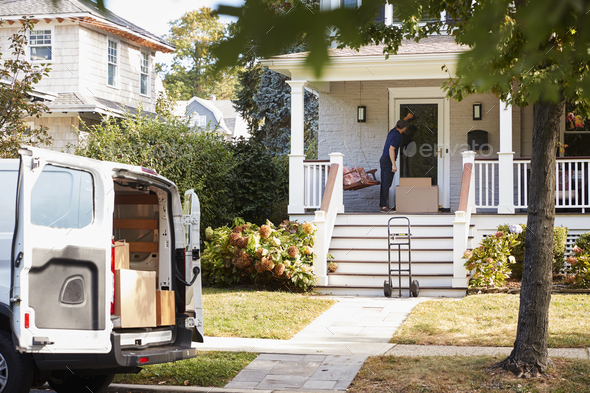 Courier Using Trolley To Deliver Package To House - Stock Photo - Images