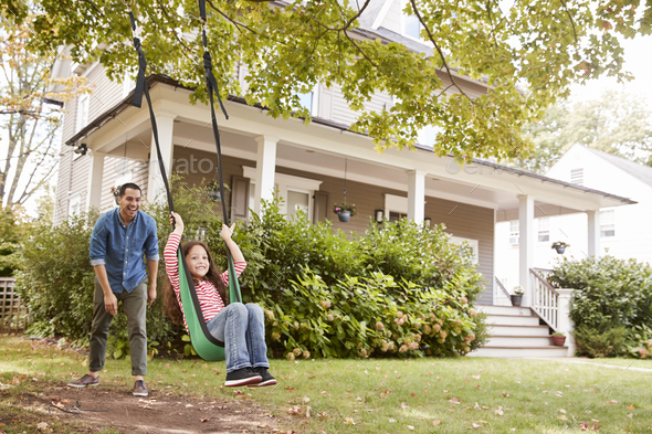 Father Pushing Daughter On Garden Swing At Home - Stock Photo - Images