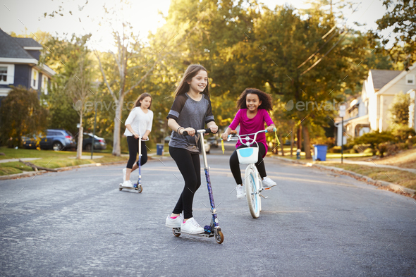 Three girls riding down the street on scooters and a bike - Stock Photo - Images