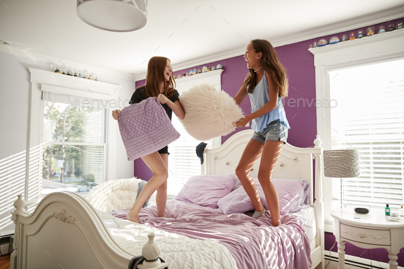 Two teenage girls standing on a bed having a pillow fight - Stock Photo - Images