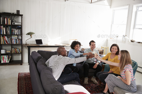 Five friends making a toast in a New York loft apartment - Stock Photo - Images