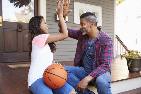 Father And Daughter Discussing Basketball On Porch Of Home - Stock Photo - Images