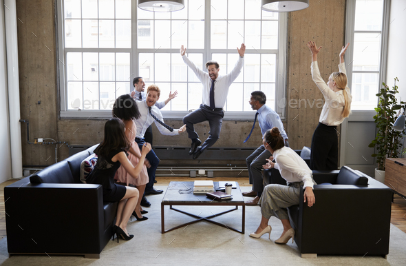 Business team jump for joy at hitting target in meeting - Stock Photo - Images