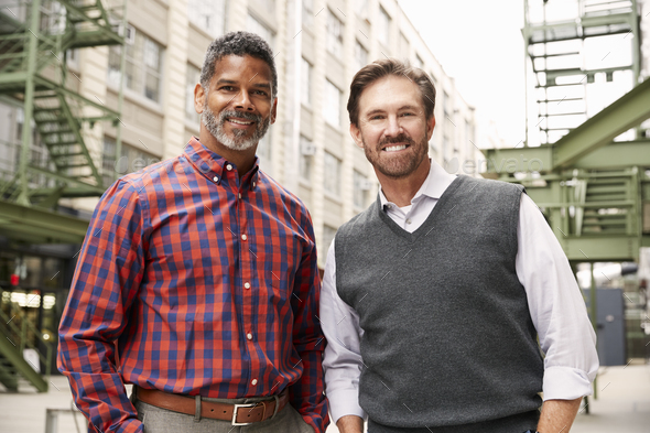 Two middle aged make colleagues outside their workplace - Stock Photo - Images