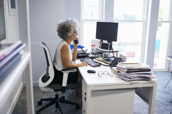 Middle aged businesswoman using the phone in her office - Stock Photo - Images