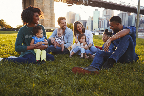 Two families with daughters sitting on lawn - Stock Photo - Images