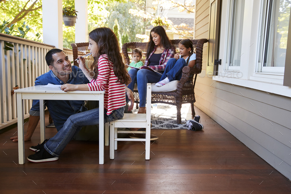 Family Sit On Porch Of House Reading Books And Playing Games - Stock Photo - Images