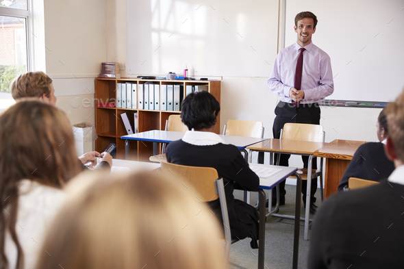 Teenage Students Listening To Male Teacher In Classroom - Stock Photo - Images