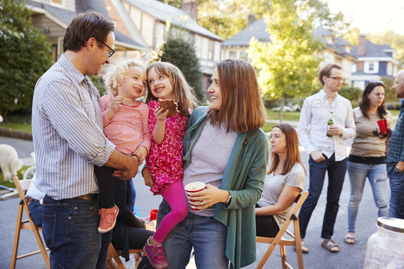 Parents holding their young kids while they eat at a block party - Stock Photo - Images