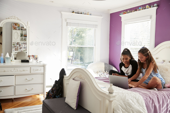 Two girlfriends in bedroom sitting on bed using a laptop - Stock Photo - Images
