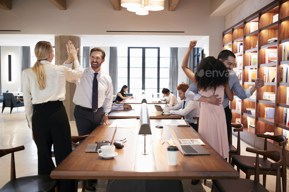 Four colleagues celebrating success in an open plan office - Stock Photo - Images