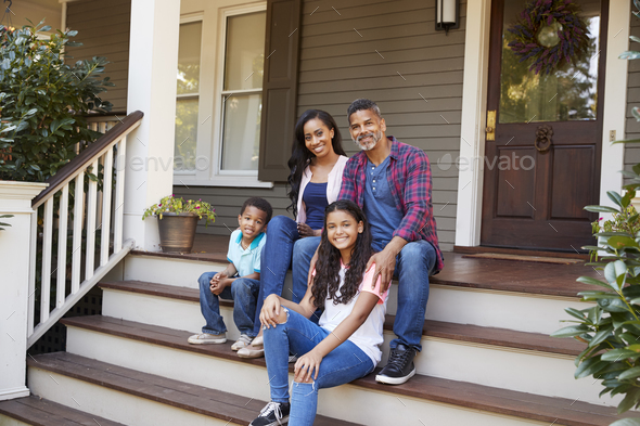 Family With Children Sit On Steps Leading Up To Porch Of Home - Stock Photo - Images