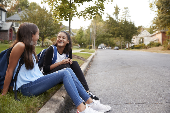 Two teen girlfriends sit talking at the roadside - Stock Photo - Images