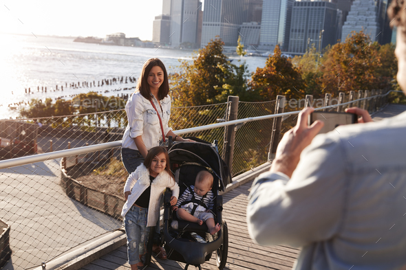 Young family with two daughters taking a photo on footbridge - Stock Photo - Images