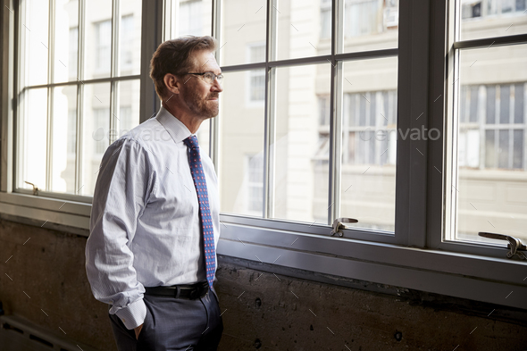 Senior businessman looking out of window, hands in pockets - Stock Photo - Images