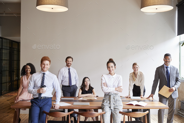 Young professionals at a business meeting looking to camera - Stock Photo - Images