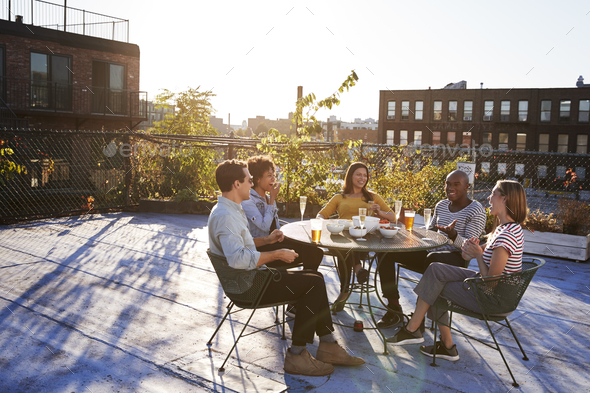 Five friends sit talking at a table on a New York rooftop - Stock Photo - Images