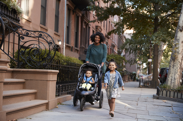 Mother and two daughters taking a walk down the street - Stock Photo - Images