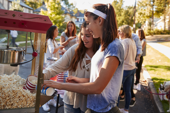 Girls serve themselves popcorn at neighbourhood block party - Stock Photo - Images