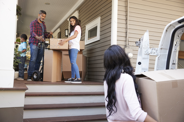 Children Helping Children With Boxes On Moving In Day - Stock Photo - Images