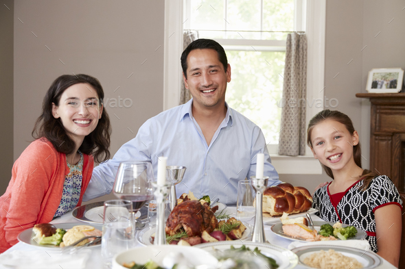 Jewish family at Shabbat dinner table smiling to camera - Stock Photo - Images