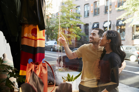 Smiling couple pointing at clothes in a shop window - Stock Photo - Images