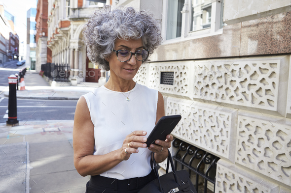 Middle aged woman using smartphone in city street - Stock Photo - Images