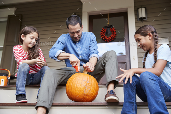 Father And Daughters Carving Halloween Pumpkin On House Steps - Stock Photo - Images