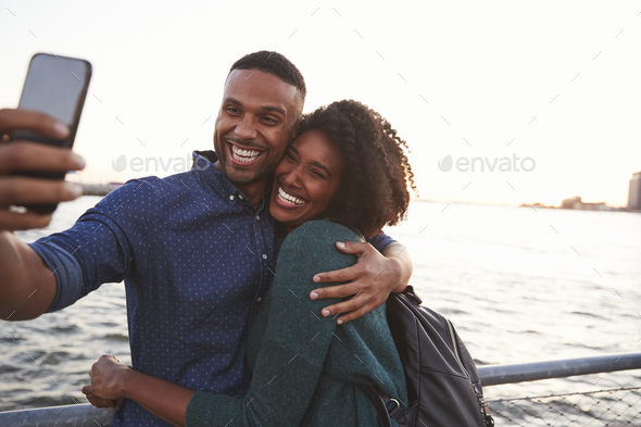Young black couple taking photo on quayside, front view - Stock Photo - Images