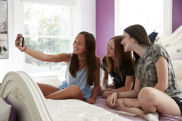 Teenage girls sitting on a bed together taking a selfie - Stock Photo - Images