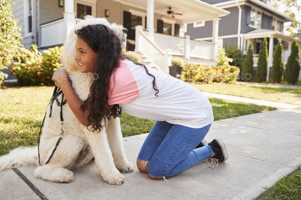 Girl Walking Dog Along Suburban Street - Stock Photo - Images
