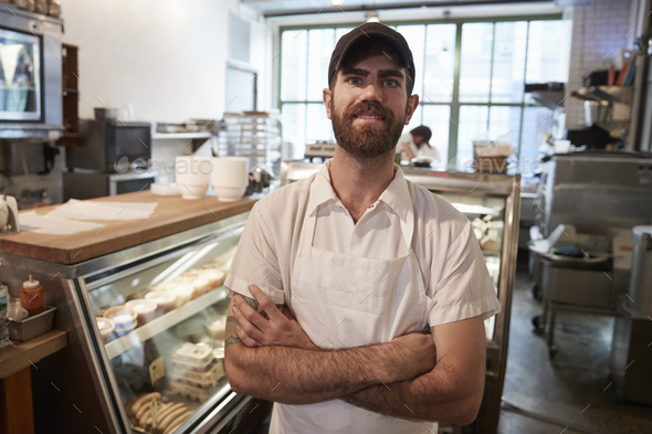 Young bearded butcher smiling to camera in his shop - Stock Photo - Images